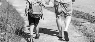 Boy and adult walking and holding hands